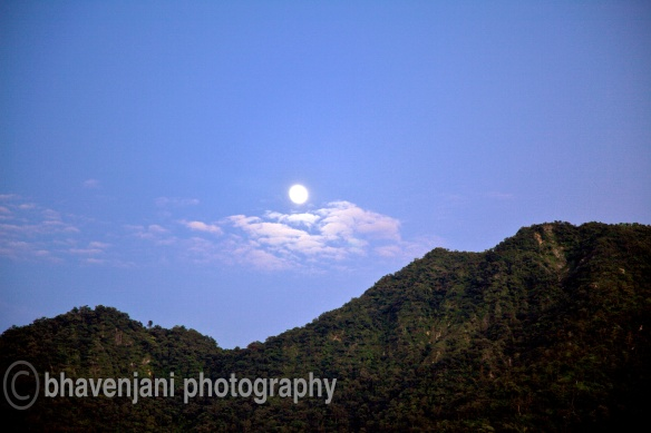 The full moon rises from behind the hills in Rishikesh