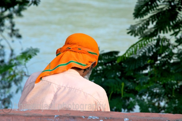 A man in a saffron head cloth sits and meditates on the banks of the river Ganges