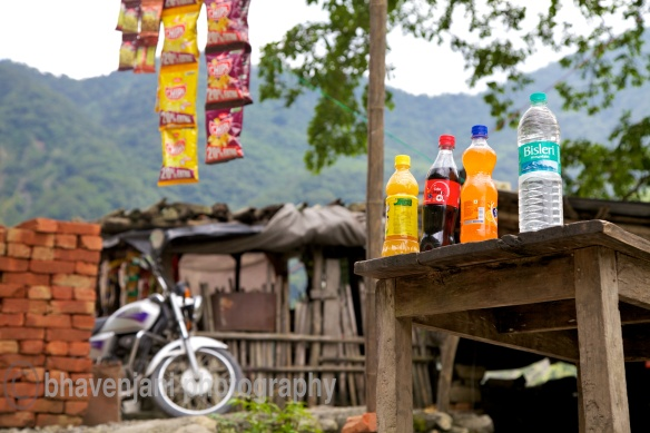 Picture of a motor bike, potato chip packets and soft drinks with rugged hills in the background