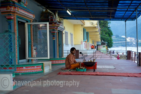 A holy man sits in front of a mic as he prepares for the evening prayers