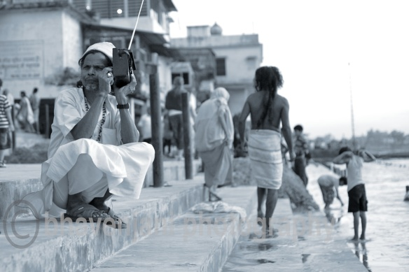 A sadhu (holy man) listens to radio sitting on the banks of river Ganges