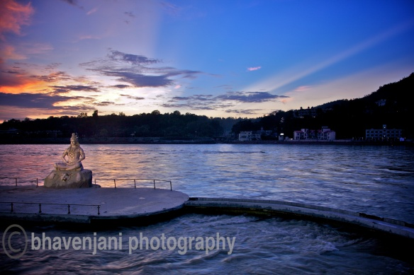 A sunset in Rishikesh renders the sky with awesome colors, with a view of Lord Shiva statue at Swargashram