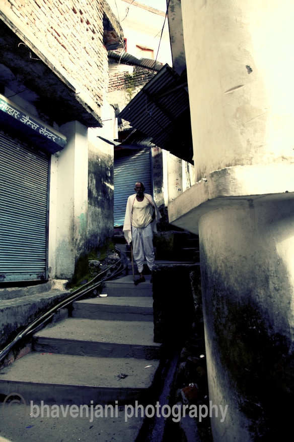 An old man walks down with support from his walking stick, on the narrow path leading to Laxman jhula