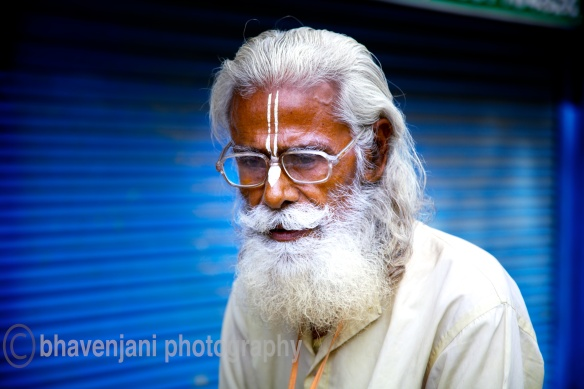 An old man lost in thought as he sits on the narrow path leading to Laxman jhula in Rishikesh