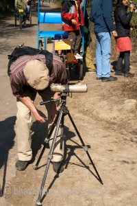 A tourist leans to look into a telescope to look at birds at Bharatpur bird sanctuary